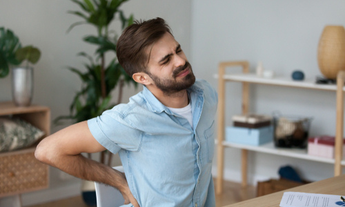 A Man Feeling Back Pain while Seated on his Chair
