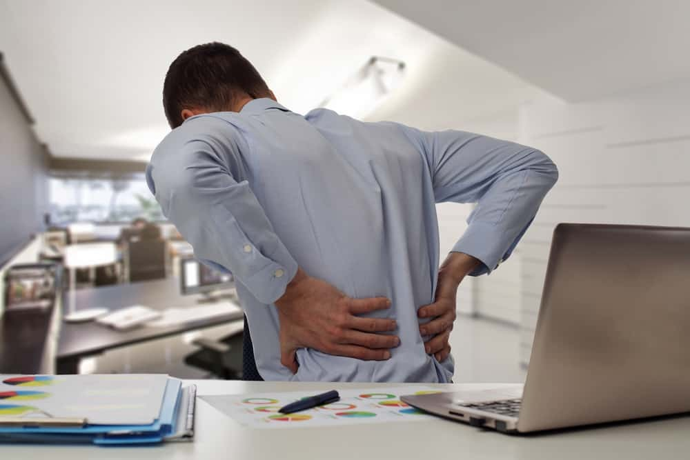 Man Grabbing his Back with Both Hands Because of Pain